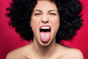 Woman sticking out her tongue - what your tongue reveals about your health