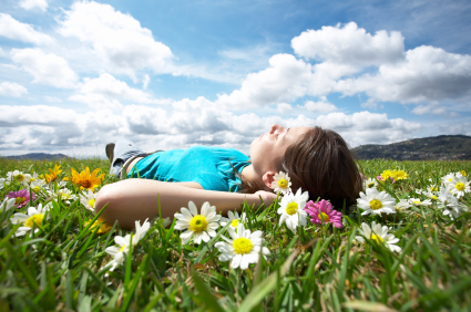 Person laying in a field of flowers looking up at the sky