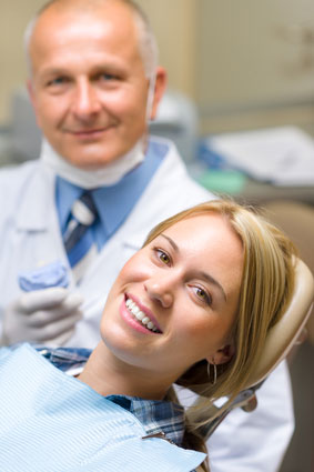 woman smiling in a dental chair with her dentist behind her