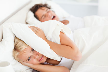 woman covering her ears with a pillow trying to block her husband's snoring