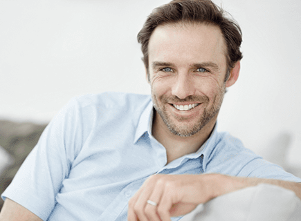 Brunette man with shadow beard smiling - perhaps after receiving cater-to-cowards dentistry